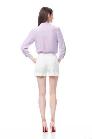Mooie sexy vrouw donkerbruin lang haar dragen lila zijden blouse en witte katoenen broek schoenen, fashion model zakelijke stijl kleren voor kantoor, toevallige ontmoeting, catalogus op een witte achtergrond collectie