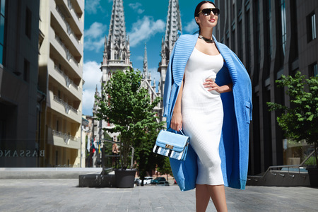 Beautiful fashion stylish female model long dark hair wearing natural make-up in chic slinky dress Knit long coat jacket accessory sunglasses bag shoes jewelry vintage city church modern building