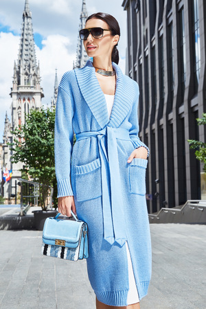 Beautiful sexy fashion stylish female model long dark hair wearing natural make-up in chic slinky dress Knit long coat jacket accessory sunglasses bag shoes jewelry vintage city church modern building
