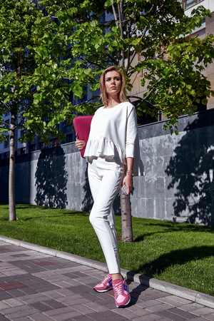 talk big: Super busy business woman walk on the street in big city talk on phone hold tab wear fashion white suit and sneakers car building model withe long blond hair walk life style office every day date meet
