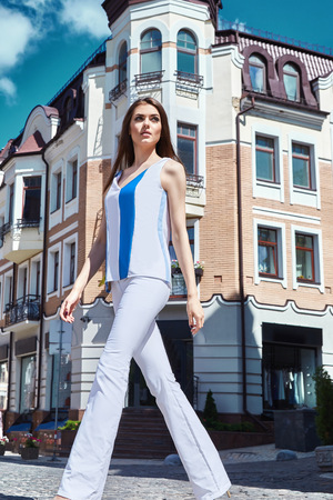 blouse sexy: Sexy beautiful woman walk on the city street building fashion luxury style for party date glamour pose summer clothes collection brunette hair accessory model wear blue  cotton jeans and blouse hairdo