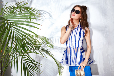 chic woman: Sexy beautiful woman luxury chic fashion gold sunglasses brand hand bag trendy jewelry style for party date glamour pose summer palm clothes collection brunette hair accessory model Stock Photo