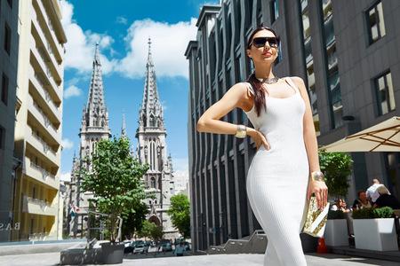 Mujer atractiva del encanto en blanco vestido de estilo de la moda con el accesorio bolso y edificios a pie de joyas de oro y árboles empresaria usar zapatos calle morena plantean reunión fecha de partido de la señora del maquillaje