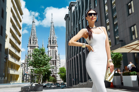 Sexy glamour woman in white fashion style dress with handbag accessory and golden jewelry businesswoman walk buildings and trees street brunette wear shoes makeup lady date party meeting pose Фото со стока