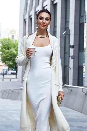 Beautiful sexy fashion glamour woman walk city street church modern building architecture dark hair natural makeup chic slinky dress knit wool long coat jacket accessory cup of coffee bag  jewelry