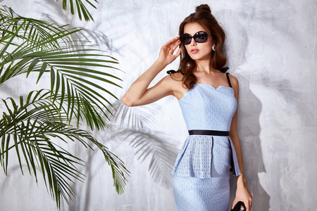 Sexy beautiful woman luxury chic fashion gold sunglasses brand hand bag trendy jewelry style for party date glamour pose summer palm clothes collection brunette hair accessory model Banque d'images