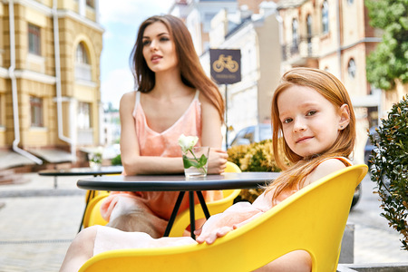 Madre e hija sentada en tiempo de verano café de la calle día familia feliz hermoso lindo y niña pequeña en el restaurante para el desayuno por la mañana de fiesta vestido de la manera mirada edificios mamá del bebé