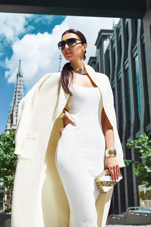 Beautiful sexy fashion glamour woman walk city street church modern building architecture dark hair natural makeup chic slinky dress knit wool long coat jacket accessory sunglasses bag shoes jewelry
