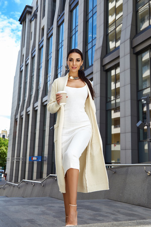 Beautiful sexy fashion stylish female model long dark hair wearing natural make-up in chic slinky dress Knit long coat jacket accessory cup of coffee bag shoes jewelry vintage city modern building Stock Photo