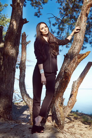 avantegarde: Beautiful sexy model brunette nature wood tree water lake wear clothes black suit accessory fashion style summer woman walk