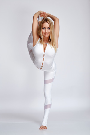 Sexy beautiful blond woman with perfect athlete figure dance gymnastics exercise stretching, trainer, fitness, yoga health wear sports in gym dressed in comfortable casual clothes relaxes meditation. Stock Photo