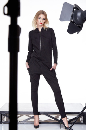 party wear: White background studio beautiful woman lady spring autumn collection glamor model fashion clothes wear casual style for date party black color suit pants pretty face blond natural hair.