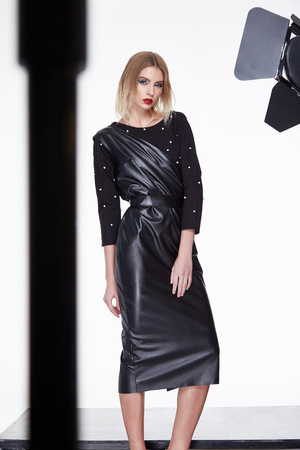 party wear: Beautiful sexy woman blond hair fashion model wear stylish black lather dress summer collection glamour pose studio makeup red lips style clothes for party casual perfect lady chic vogue. Stock Photo