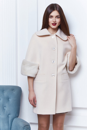 Business woman wear casual clothes style for winter autumn fashion model natural cashmere wool coat brunette hair glamour trend studio white background trench beautiful girl makeup room chair. Stock Photo