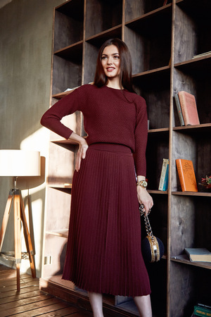 party wear: Beautiful sexy woman brunette hair fashion model wear stylish red dress wool sweater skirt  casual collection glamour pose studio makeup cosmetic style clothes for party perfect lady chic vogue coffee. Stock Photo