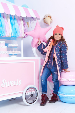 Beautiful cute pretty little girl baby blond curly hair fun to play in the children room candy bar birthday party wear in denim jeans jacket cap style fashion clothing collection daughter macaroon.