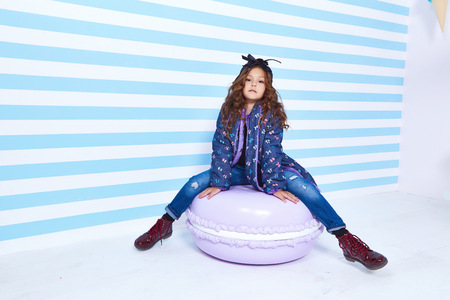 Beautiful cute pretty little girl baby blond curly hair fun to play children room candy birthday party striped background wear in denim jeans jacket style fashion clothes winter collection macaroon.