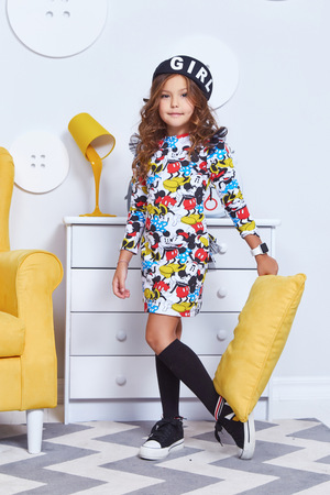 Cute little baby girl fashion pretty model dark blonde curly lady hair funny child birthday party fun children room yellow chair interior play pillow fight wear style clothes dress shoes decoration.