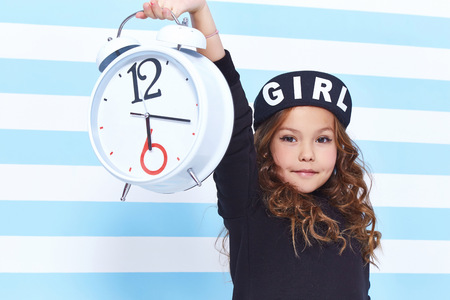 vestidos de epoca: Beautiful cute pretty little girl baby blond curly hair fun to play children room party striped background wear dress style fashion clothes winter collection watch alarm Alice in Wonderland daughter.