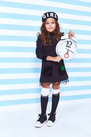 Beautiful cute pretty little girl baby blond curly hair fun to play children room party striped background wear dress style fashion clothes winter collection watch alarm Alice in Wonderland daughter.