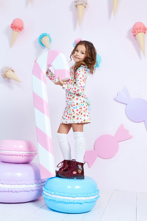 Cute little baby girl fashion pretty model dark blonde curly lady hair funny child birthday party fun children room candy bar sweet ice cream play with toy wear style clothes dress shoes decoration. Archivio Fotografico