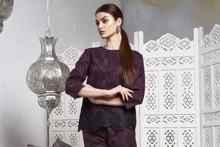 Beautiful sexy woman brunette hair east style arabic morocco furniture glamour model pose fashion clothes skinny silk cotton suit trousers blouse accessory hand bag make up pretty face party office.