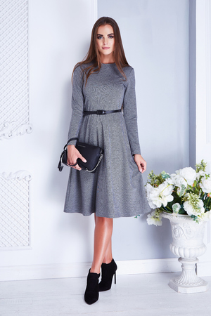 Beautiful sexy brunette woman wear elegant fashion silk dress hold small bag high heels clothes for date meeting summer collection model in white room interior sofa wall vase and flower casual style.