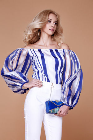 Sexy beautiful pretty young woman long blond curly hair slinkybody shape natural organic make up wear fashion clothes silk blouse cotton trousers hold hand bag accessory jewelry model glamour style. Фото со стока