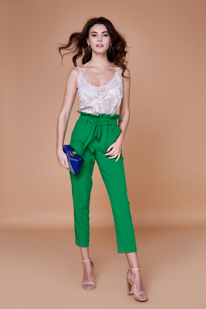 Beautiful young sexy girl with long wavy brunette hair with a bright evening make up perfect summer tan thin figure dressed in colored silk blouse green pants high heels shoes perfect body shape bag.