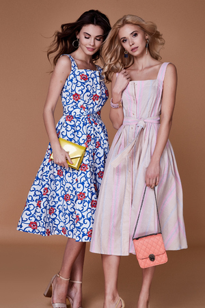 Two beauty woman model wear stylish design trend clothing cotton dress casual summer style for date meeting walk party long blond brunette hair makeup party businesswoman accessory bag fashion friend.