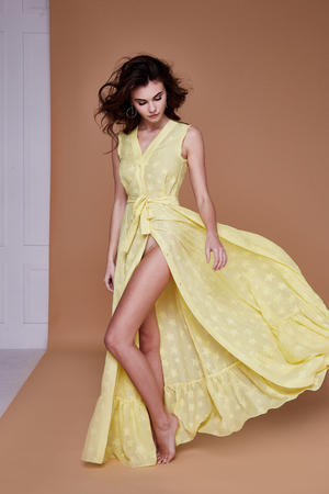 Sexy beauty woman pretty face tan skin wear yellow silk dress long skinny body shape makeup cosmetic summer collection studio catalog brunette curly hair clothes for date meeting walk beach fashion. Stock Photo