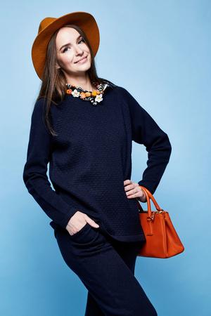 女性ファッション モデル グラマー ポーズ ウール カシミヤ衣料品スーツのズボン セーター濃紺色の小物を持っていたバッグ ジュエリー ネックレス スポーツ摩耗徒歩かなり顔長いブルネットの髪化粧のカジュアル スタイル。 写真素材 - 78613381