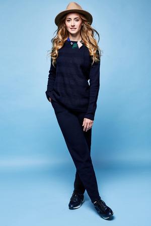 女性服ウール カシミヤ スーツ ズボン セーター紺色アクセサリー ジュエリー ネックレス ファッション モデル ポーズ スポーツ摩耗カジュアル スタイル徒歩かなり顔長いブロンドの巻き毛化粧化粧品女性を持っていた。 写真素材 - 78613046