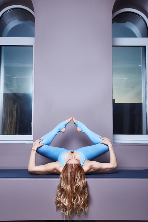Beautiful young sexy blond woman with a sport physique slender shape doing yoga exercises  fitness in skinny blue suit meditates relaxes pilates healthy lifestyle window room meditation relax.
