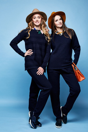 Two pretty woman wear wool cashmere suit pants sweater dark blue color accessory had bag jewelry necklace fashion model sport clothes casual style pretty face blond brunette hair makeup friend sister.