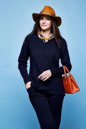 女性ファッション モデル グラマー ポーズ ウール カシミヤ衣料品スーツのズボン セーター濃紺色の小物を持っていたバッグ ジュエリー ネックレス スポーツ摩耗徒歩かなり顔長いブルネットの髪化粧のカジュアル スタイル。 写真素材 - 78839426