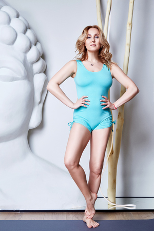 Sexy beautiful woman blond hair sporty body shape yoga, exercise or fitness,athletic, gymnastic, healthy lifestyle, dressed in comfortable casual clothes sport pilates diet white studio buddha east. 版權商用圖片