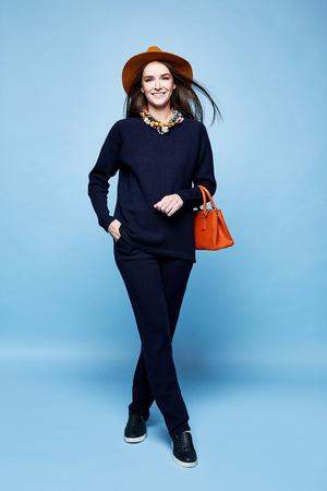 女性ファッション モデル グラマー ポーズ ウール カシミヤ衣料品スーツのズボン セーター濃紺色の小物を持っていたバッグ ジュエリー ネックレス スポーツ摩耗徒歩かなり顔長いブルネットの髪化粧のカジュアル スタイル。 写真素材 - 79540051