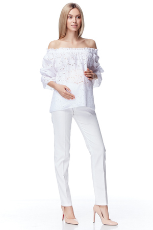 Beautiful elegant pregnant woman blond hair wear style fashion blouse pants mother hold in hand tummy wait for baby child new born pretty lady clothes for pregnancy white background collection heath.