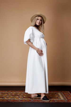 De mooie elegante zwangere van de de slijtagestijl van het vrouwen blonde haar de manier lange witte kleding voor de in hand buik van de moeder wacht op kleren van de baby de mooie dame voor achtergrond van de het tapijtinzameling van de zwangerschap de beige. Stockfoto