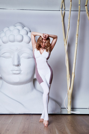 Beautiful sexy blonde with perfect athletic slim figure engaged in yoga, pilates, exercise or fitness, lead healthy lifestyle, and eats right relaxes meditation care relax gym suit nylon exercise. Imagens
