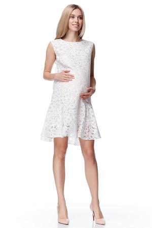美しいエレガントな妊婦ブロンドの髪を着るスタイル ファッションは手におなかを待つ妊娠ホワイト バック グラウンド コレクション ヒースのかな
