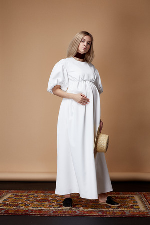 Beautiful elegant pregnant woman blond hair wear style fashion long white dress for mother hold in hand tummy wait for baby pretty lady clothes for pregnancy beige background carpet collection heath.