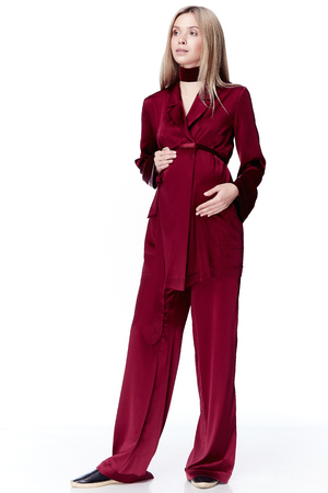 妊娠中の女性ブロンドの髪服スタイル ファッション赤いシルク スーツ × 母の保持手でおなか生まれ新しい赤ん坊を待つきれいな女性服妊娠ホワイ