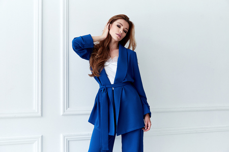 Fashion glamour sexy model beautiful woman pretty face long bold hair skin care perfect body shape white background makeup lady wear blue suit style clothes for office party walk celebrity accessory.