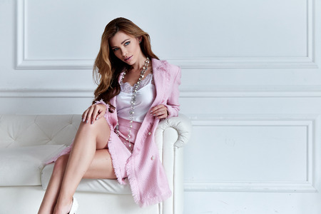 Beauty woman model wear stylish design trend clothing silk pink jacket suit skirt casual formal office style walk party long blond hair party businesswoman secretary diplomatic protocol room sofa. 스톡 콘텐츠