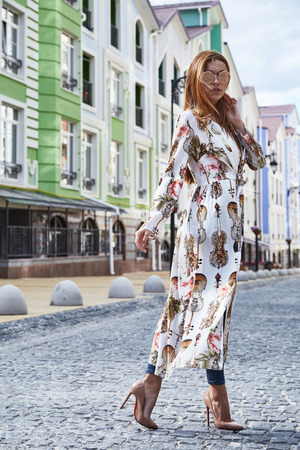 Woman walk on the street city style fashion casual elegant high heel catalog of clothes beautiful lady romantic date accessory sunglasses summer silk dress luxury lifestyle. Stock fotó