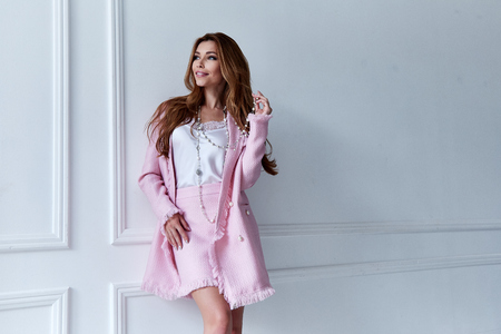Beauty woman model wear stylish design trend clothing silk pink jacket suit skirt casual formal office style walk party long blond hair makeup party businesswoman secretary diplomatic protocol room. Stock Photo
