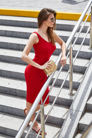 Elegant sexy business woman walk down the stairs on the street summer weather wear skinny red dress casual look party romantic date glamour fashion model pose beautiful face accessory bag sunglasses.