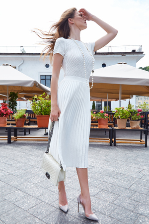 Brunette sexy woman fashion style street look elegant walk cafe restaurant date meeting businesswoman success wear white dress accessory bag sunglasses high-heels shoes clothes summer collection. Stock Photo